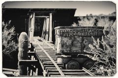 Black and White Sepia Vintage Photo of Goldfield Gold Mine`s old dangerous entrance to a gold mine shaft with trolley royalty free stock image