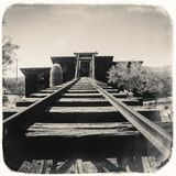 Black and White Sepia Vintage Photo of Goldfield Gold Mine`s old dangerous entrance to a gold mine shaft with trolley royalty free stock photo