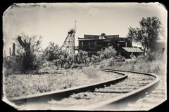 Black and White Sepia Vintage Photo of Old Train tracks in Goldfield Gold Mine Ghost Town in Youngsberg, Arizona. USA surrounded by desert, during sunny day stock image