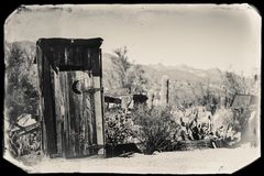 Black and White Sepia Vintage Photo of Old Western Dry Toilette in Goldfield Gold Mine Ghost Town in Youngsberg. Arizona, USA surrounded by cactuses royalty free stock photos