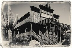 Black and White Sepia Vintage Photo of Old Wild Western Wooden Saloon in Goldfield Gold Mine Ghost Town. In Youngsberg, Arizona, USA surrounded by cactuses royalty free stock images