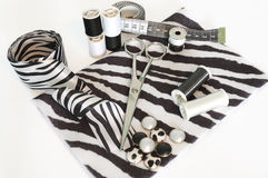 Black and white sewing and scrapbooking items. With various buttons, spools, threads, ribbons, measuring tapes,  scissors and textile close up on white Royalty Free Stock Photography