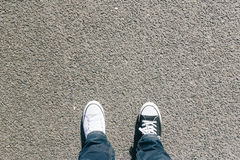 Black and white shoes on asphalt, high angle Stock Photo