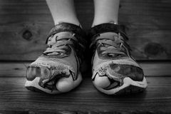 Black and White Shoes Holes Toes Sticking Out. Black and white photo of shoes with holes in them and toes sticking out child kid young Royalty Free Stock Images