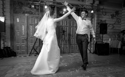 Black and white shot of bride and groom dancing at hall Royalty Free Stock Photos