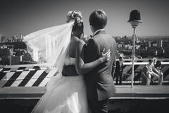 Black and white shot of bride and groom looking at urban city Stock Photos