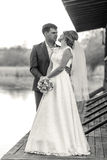 Black and white shot of bride and groom posing on pier at river Royalty Free Stock Images