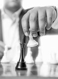 Black and white shot of businessman beating chess king with pawn Stock Photos