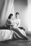 Black and white shot of elegant pregnant couple relaxing on bed Royalty Free Stock Photos