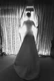 Black and white shot of elegant young bride in front of big wind Stock Images
