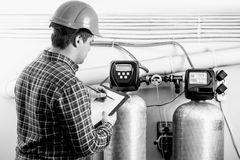 Black and white shot of inspector checking factory equipment Royalty Free Stock Images