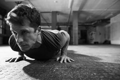 Black And White Shot Of Man In Gym Doing Press-Ups Stock Images
