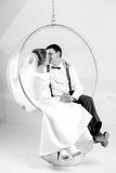Black and white shot of newly married couple kissing on swing at Stock Image