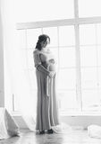 Black and white shot of pregnant woman posing against big window Stock Images