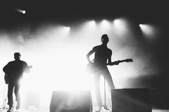 Black and white shot of rock band in a stage backlights. Rock band silhouettes on a stage in a bright stage lights. Black and white Stock Photo
