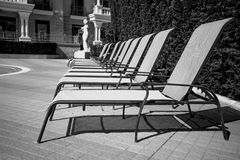 Black and white shot of row of sunbed chairs at pool Royalty Free Stock Image