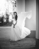Black and white shot of wind lifting brides white dress Royalty Free Stock Photos