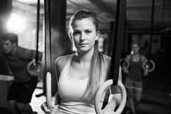 Black And White Shot Of Woman Using Gymnastic Rings In Gym Stock Photo