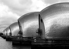 Black and white side view of The Thames Barrier. With a moody sky in the background Stock Images