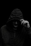 Black and white Silhouette of a hooded man, on black. royalty free stock images