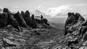 Black and white silhouette of the tourist on the peak of the mountain royalty free stock images