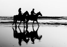 Black and White Horses on the Beach. A black and white silhouette of two horses with a girl and a man riding in the surf of a beach royalty free stock images