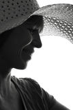 Black and white silhouette of a woman in a summer hat. Black and white fashion portrait silhouette of a young woman in a hat with a sincere smile on her face Royalty Free Stock Images