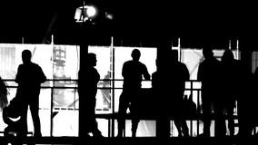 Black White silhouettes of people dancing on the balcony. Fast moving. Black White silhouettes of people have fun on the balcony against a bright white wall stock video