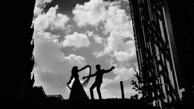 Black and white silhouettes of two people in love dancing against the beautiful sky. Beautiful stylish frame! wonderful color stock video