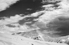 Black and white ski slope and sky with clouds in evening Royalty Free Stock Photos