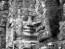 Black and white smiling faces carved into the rock at Bayon Temple, Angkor Wat Cambodia. Stock Photos