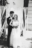 A black and white of smiling newlyweds standing in the garden Royalty Free Stock Photos