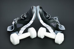 Black-and-white sneakers and white dumbbells against a dark back Stock Photo