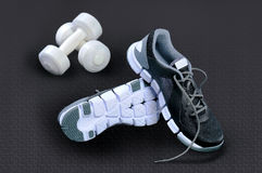 Black-and-white sneakers and white dumbbells against a dark back Stock Image