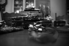 Black and White Stack of Christmas Presents. Pile of Christmas presents with ribbons and bows on a wooden table. Black and white royalty free stock photo