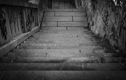 Black and white stairs going down with a lot grafiti. Close royalty free stock photo