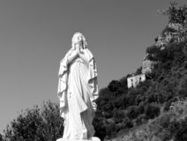 Black and white statue of the Virgin Mary praying stock images
