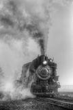 Black and white steam locomotive. Black and white photo of restored steam locomotive venting steam as it approaches station Stock Image