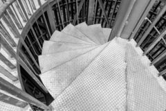 Steel spiral staircase. Black and white of Steel spiral staircase with steel battens on natural background royalty free stock images