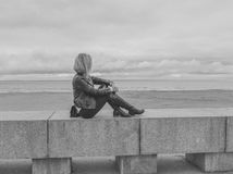 Black and white girl sitting on the stone pavement by the sea. Black and white,on the stone pavement by the sea, sits a girl Stock Photos