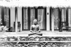 Black and white stone statue of Buddha sitting and meditating in the tropical spa garden royalty free stock photography