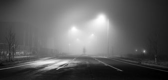 Black and white street at night with fog Stock Images