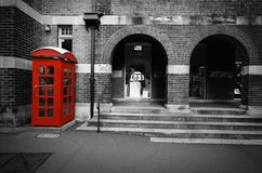 Black and white street scene with selective color on a red phone box in Sydney, Australia Royalty Free Stock Images