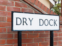 a black and white street sign saying dry dock with brick background attached to poles into the ground on the path and road royalty free stock photo