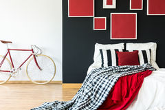 Minimalist bedroom with red bike. Black and white striped pillows on a king-size bed in a minimalist bedroom with red bike Stock Photo