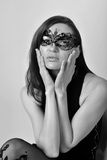 Black and white studio portrait of beautiful model posing pretty wearing dress and mask. Royalty Free Stock Photo