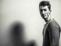 Black-white studio portrait of young handsome man in knitted sweater. Close-up photo. Stock Images