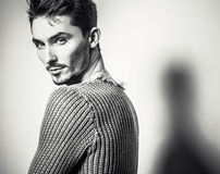 Black-white studio portrait of young handsome man in knitted sweater. Close-up photo. Royalty Free Stock Photo