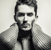 Black-white studio portrait of young handsome man in knitted sweater. Close-up photo. Stock Photography