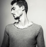 Black-white studio portrait of young handsome man in knitted sweater. Close-up photo. Stock Image